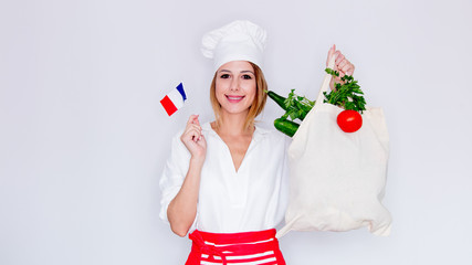 woman in cook uniform holding bag with different vegetables and french flag