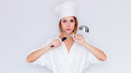 woman in cook uniform holding kitchenware on white background
