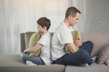 I do not talk with you anymore. Upset man and boy turning back to each other while situating on couch. They are keeping pillows in arms