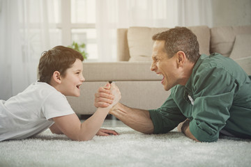 Joyful man and boy are competing in arm wrestling while lying on carpet in living room. Child is looking at dad and smiling