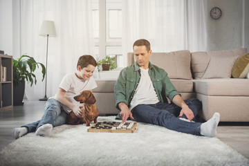 Pensive man is moving checker on board and smiling. His son is sitting near him on carpet and stroking the dog