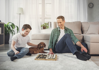 Joyful father and son are paying checkers together at home. The dog is lying on floor near them