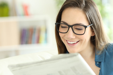 Lady wearing eyeglasses reading a newspaper