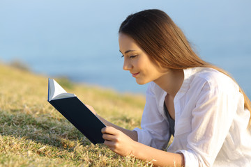 Relaxed woman reading a paper book lying on the grass