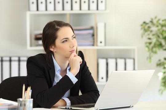 Pensive office worker wondering looking at side