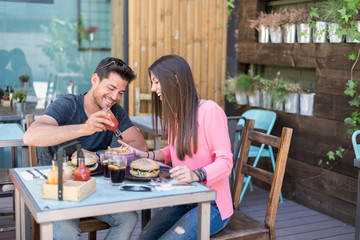Happy young couple seating in a restaurant terrace eating a burger
