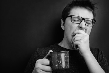 Sleepy yawning man in eyeglasses with red cup of tea or coffee has uncombed hair in underwear on black background, morning refreshment and drink. Copy space for your text. black and white photo