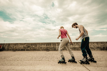 Two people race together riding rollerblades.