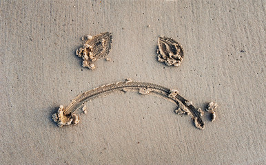 Upset smiley with sad eyes painted on the sand. Depression concept. Ban on bathing. Quarantine.