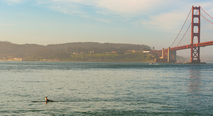 Woman rowing in the bay by the bridge with sun at her back