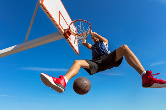 Slam Dunk. Side view of young basketball player making slam dunk