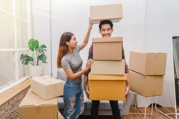 Asian young couple carrying big cardboard box for moving in new house, Helping relocate and joshing together, Moving and House Hunting concept, selective focus