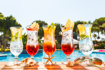Craft cocktails near the pool with sea star and sunglasses. Vacation, summer, holiday, luxury resort concept