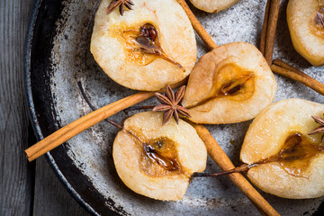 Grilled pears with cinnamon and honey on the rustic background. Selective focus.