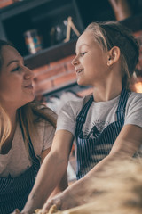 Mother and daughter looking at each other while cooking on kitchen together.
