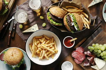 Burgers and french fries served in frying pans on wooden table with sauce, beer, salad and different snacks top view. Dinner table concept