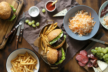 Dinner table concept. Burgers and french fries served in frying pans on wooden table with sauce, salad and different snacks top view