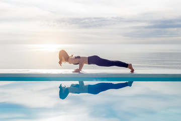 In de dag Ontspanning Asian young woman practice yoga Plank or Phalakasana Pose on the beach with beautiful sea,Feeling so comfortable and relax in holiday