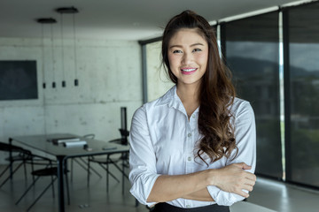 Business Asian woman wearing white shirt smile and cross arm in modern office,Business and Startup Concept