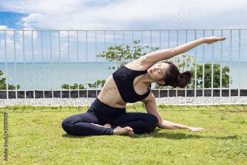 a79c8111670 Happy Asian woman wearing black sport wear practice yoga Seated side  stretch pose with beautiful sea