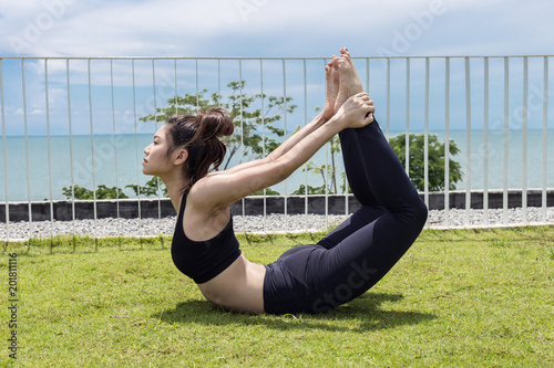 3e46c64239f Happy Asian woman wearing black sport wear practice yoga bow or dhanurasana  pose with beautiful sea