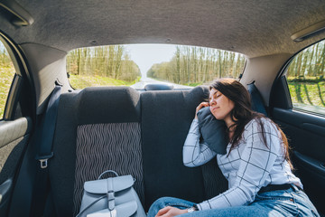 young woman sleeping in car on backseats. travel concept