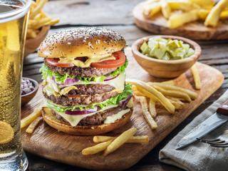 Big hamburger and French fries on the wooden tray.