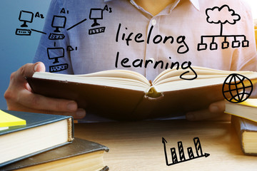 Lifelong learning concept. Man holding and reading the book.