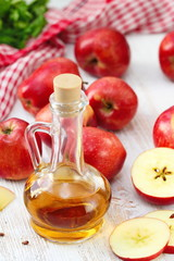 Apple vinegar. Bottle of apple vinegar on wooden background.
