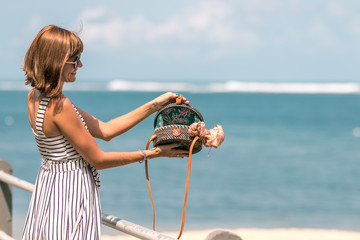 Woman hands with fashionable stylish rattan bag and silk scarf on the ocean background. Tropical island of Bali, Indonesia. Rattan handbag and silk scarf.