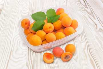 Apricots in container and beside to him on wooden surface