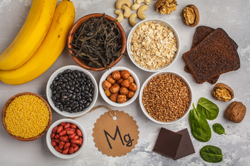 Healthy food nutrition dieting concept. Assortment of high magnesium sources. Banana chocolate spinach, buckwheat, nuts, beans, oat. White background, top view