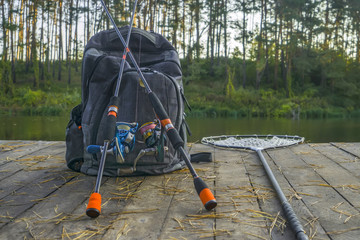 Fishing background of spinning rod with reel and landing net on wood boards on lake in forest