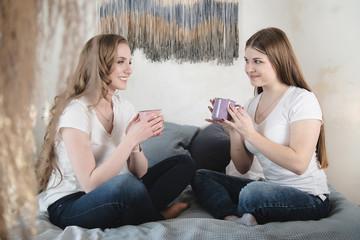 Two beautiful female friends are having fun indoors. Female friendship