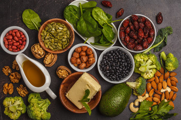 Healthy food nutrition dieting concept. Assortment of high vitamin E sources. Oil, nuts, avocado, butter, healthy fats, rose hips, parsley, seeds, spinach. Dark background, top view