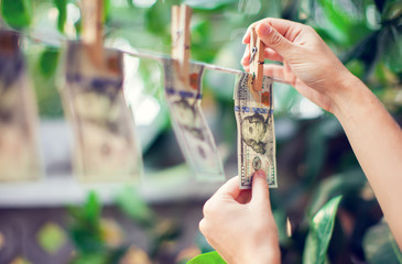 US dollar banknotes hanging on rope for money laundering conept hand collect money