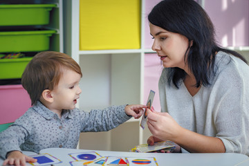 Mother or the teacher teaches the child showing the picture