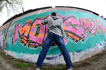 A young guy in a gray hoodie paints graffiti in pink and green colors on a wall in rainy weather....