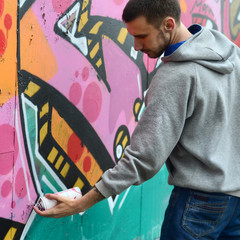 A young guy in a gray hoodie paints graffiti in pink and green colors on a wall in rainy weather