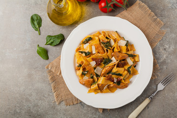 Italian salad, pappardelle pasta, with spinach, grilled chicken and dried tomatoes, sprinkled with flakes of cheese.