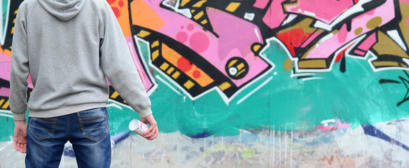 A young graffiti artist in a gray hoodie looks at the wall with his graffiti in pink and green...