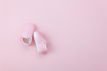 Table top view aerial image of kid fashion background concept.Flat lay shoe baby on modern beautiful rustic pink paper at office desk.Free space for creative design text and wording.Pastel tone