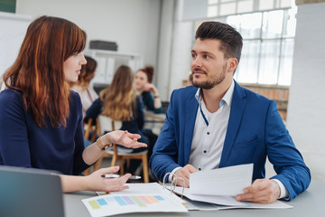 Woman discussing with man over project at office