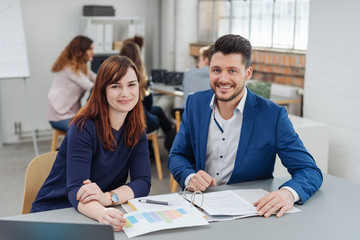Young woman working with co-working man in office