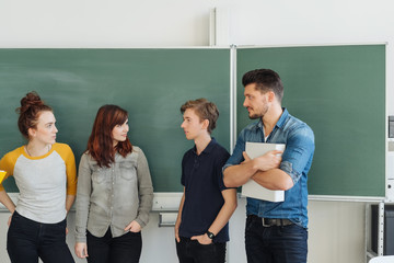Group of students talking with teacher in class