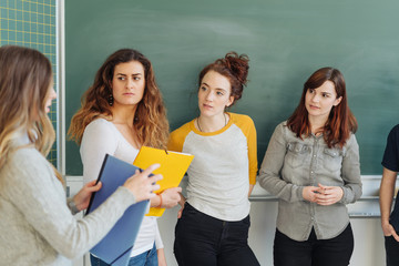 Students discussing with teacher in classroom