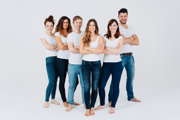 Group of friendly barefoot young friends in jeans