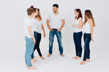 Five barefoot young men and women in jeans