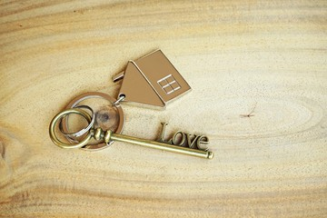 Home key with house keyring on wood background