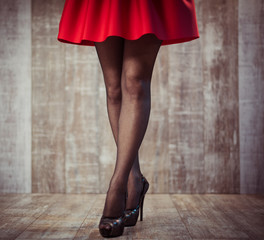 young woman legs in black stockings and red skirt on wooden background